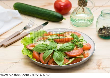 Traditional Salad Made Of Slices Of Cucumber, Tomatoes And Sesame Seeds On A Plate And Ingredients F