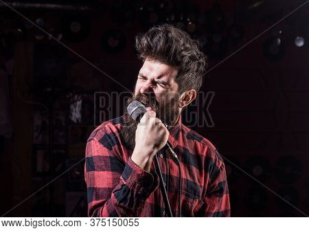 Talent Show Concept. Man With Tense Face Holds Microphone, Singing