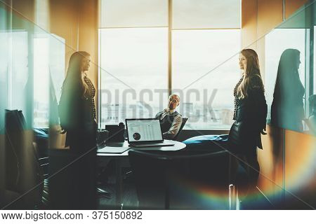 Boardroom Of Contemporary Luxury Office High-rise During A Business Meeting With Silhouettes Of Two