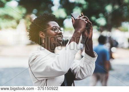 Young Happy African Female Is Photographing Sightseeing Outdoors Using Her Cellphone; Beautiful Blac