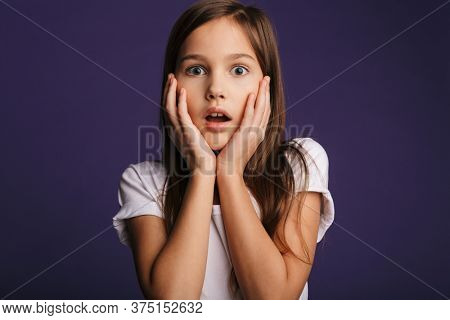 Photo of astonished pretty girl expressing shock on camera isolated over purple background