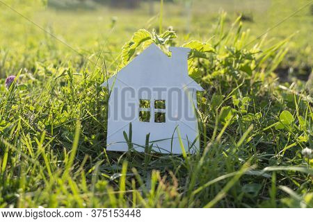 House With A Window On The Green Grass In The Sunset. Eco-bio Building. Concept Of Eco-home.
