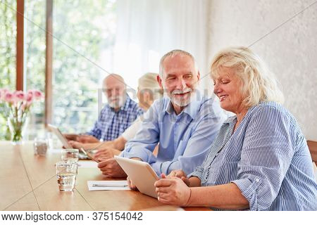 Seniors have fun while learning together in the computer course at the retirement home