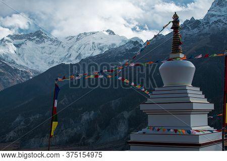Buddhist Stupa With Prayer Flags Over Manang Mountain Village, Trekking Annapurna Circuit, Nepal