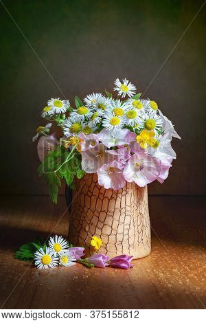 Still Life With Small Wildflowers In A Ray Of Light. Bouquet Of Wildflowers In A Clay Vase. Selectiv