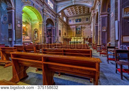 ALBA, ITALY - JUNE 07, 2020: Wooden pews in a row inside of San Giovanni Battista - ancient parish church in Alba, firstly built in 1229 and reconstructed in 1890.