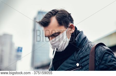Man In A Protective Mask Smokes Standing On The Street.