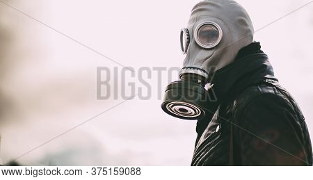 Casual Young Man In A Gas Mask Standing On The Street In An Empty City