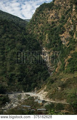 Beautiful Waterfall Flowing Under A Bridge At Annapurna Circuit, Nepal