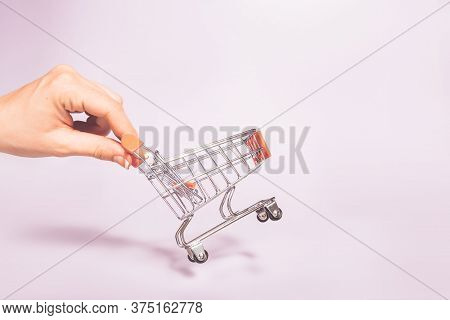 Hand Holding Empty Metal Shopping Basket. Concept Of Consumerism, Shopping Symbol. Copy Space Trend
