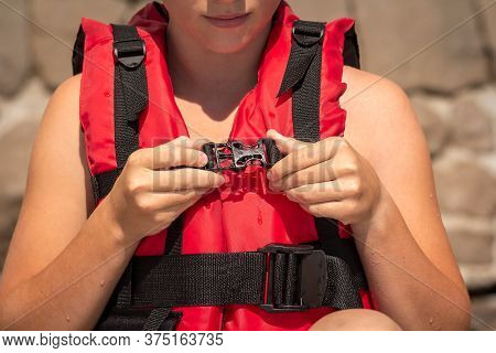 Young Girl Putting On Red Life Jacket On The Beach On A Summer Sunny Day. Female Hands Fastens Plast