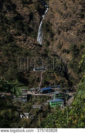 Waterfall Flowing Above A Nepalese Mountain Village At Annapurna Circuit