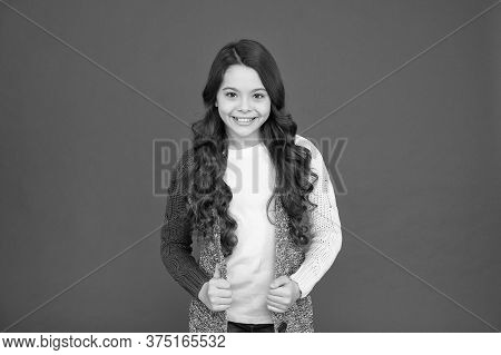 Adorable Smile. Natural Curls. Kid Cute Face Adorable Curly Hairstyle. Kid Girl Long Hair Posing Con