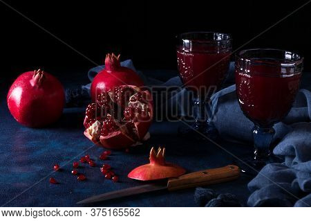 Pitcher And Two Glasses Of Fresh Pomegranate Juice, With Three Ripe Pomegranates, One Freshly Peeled