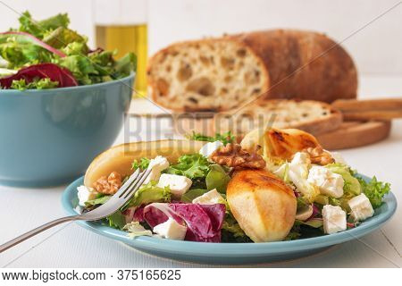 White Wooden Table With Walnut Salad, Caramelised Pears And Feta Cheese. Turquise Dishes With Salad,