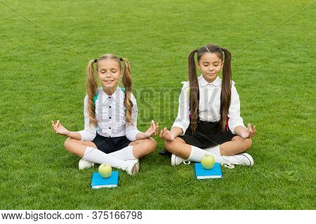 Powerful Yet Peaceful. Little Children Do Meditation On Green Grass. Small Girls Sit In Mudra Positi