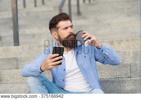 Drink It On The Go. Brutal Hipster Drink Coffee Sitting On Stairs. Bearded Man Enjoy Hot Drink Outdo
