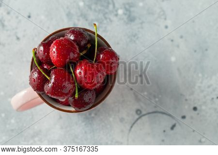 Pink Mug With Fresh Ripe Cherries. Sweet Organic Berries On A Light Concrete Background. Top View Wi
