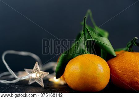 Fresh Tangerine (tangerine) With A Star Garland For Christmas Or New Year Holiday On A Black Backgro