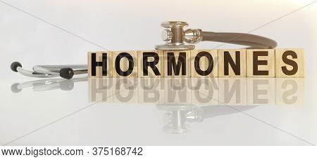 Hormones The Word On Wooden Cubes, Cubes Stand On A Reflective White Surface, On Cubes - A Stethosco