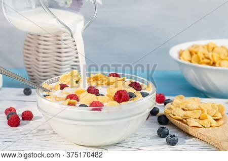 Pouring Milk Into A Cup With Cereal And Fresh Berries, Close-up. Healthy Summer Breakfast. Healthy E