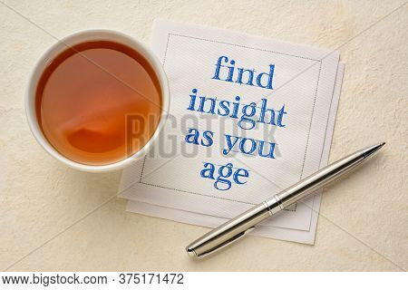 find insight as you age inspirational note - handwriting on a napkin with a cup of tea, againg well, life time experience and personal development concept