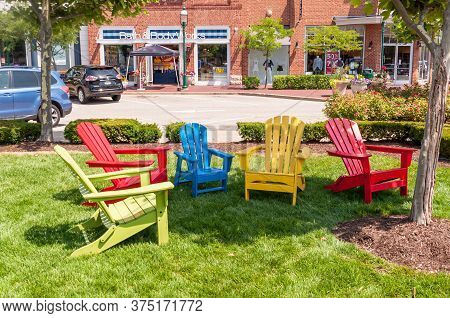 Homestead, Pennsylvania, Usa 7/5/20 Five Different Colored Adirondack Chairs In The Shade In Waterfr
