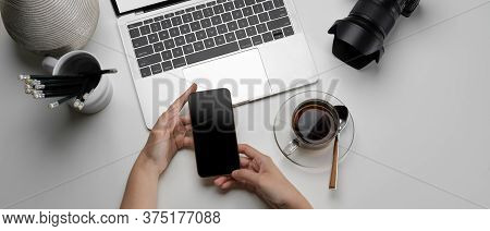 Female Working On Simple Workspace With Laptop, Camera, Stationery And Using Smartphone