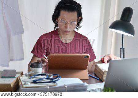 Asian Doctor Casual Wearing Researching Reading Medical Online Knowledge In Tablet To Find Treatment