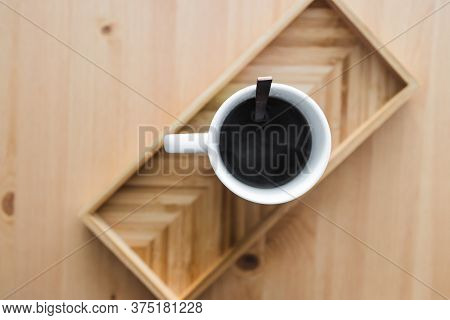 Mug Of Black Coffee On Bamboo Tray On Wooden Table
