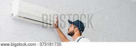 Crop Of Workman Looking At Air Conditioner On Wall