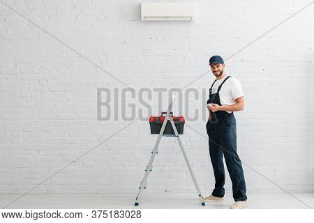 Workman Holding Remote Controller Of Air Conditioner Near Toolbox On Ladder