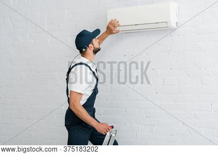 View Of Workman In Uniform Holding Screwdriver While Fixing Air Conditioner On Wall
