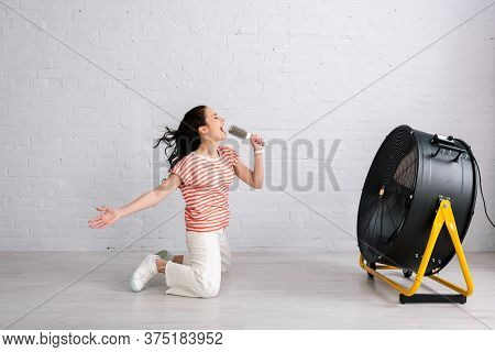 Side Of Young Woman Singing And Holding Hairbrush While Kneeling Near Electric Fan At Home