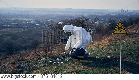 Environmentalist In Protective Suit And Gas Mask Picking Up Garbage In Abandoned Grassy Field, With