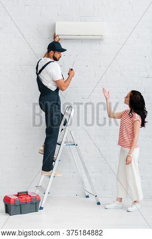 View Of Woman Pointing With Hand Near Workman Fixing Air Conditioner