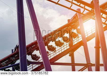 Roller Coaster In The Amusement Park With The Sunset Background.