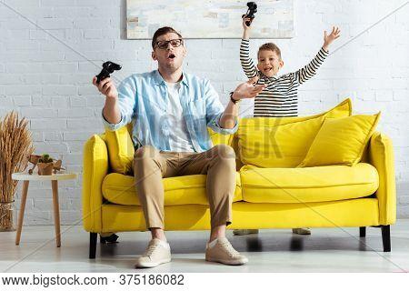 Kyiv, Ukraine - June 9, 2020: Happy Boy Showing Winner Gesture Near Discouraged Father Playing Video