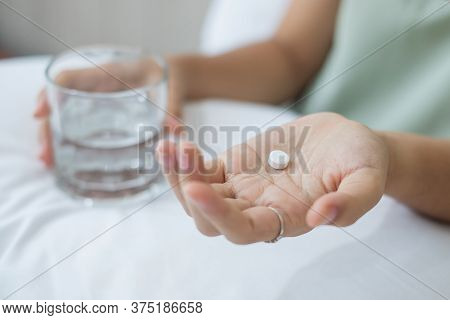 Adult Woman Holding Pill And Glass Of Water, Taking Medicine On Bed In Morning At Home. Migraine, Pa