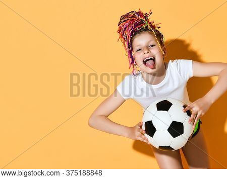 Frolic Girl With Colorful Dreadlocks Hairstyle In T-shirt And Shorts Holds Soccer Ball With Both Han
