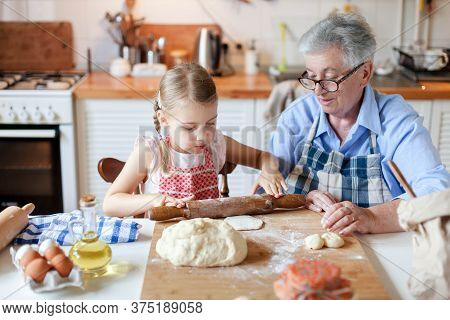 Family Cooking At Home. Grandmother And Child Making Italian Food And Meal In Cozy Kitchen. Senior W