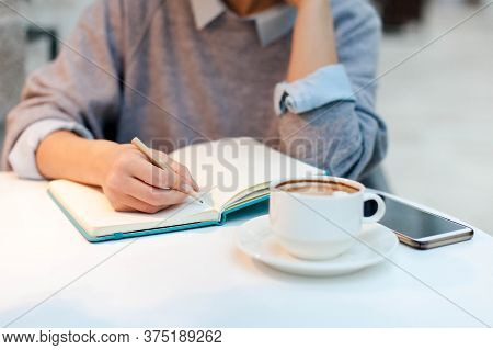 Young Woman Writing Morning Pages In Paper Notebook. Girl Sitting At Table With Cup Of Coffee And Mo