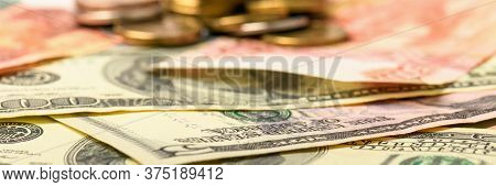 Cash Banknotes And Coins Background. The Background Of The American And Russian Money Banknotes And
