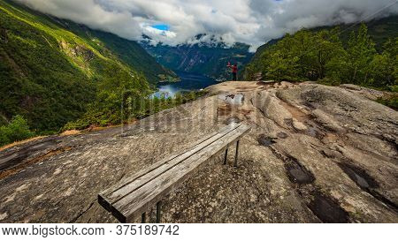 Tourist Woman Enjoying Fjord Landscape Geirangerfjord From Flydalsjuvet Viewpoint In Norway