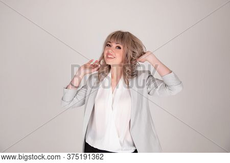 Portrait Of Woman Business Blonde In A Bright Jacket On A White Grey Background