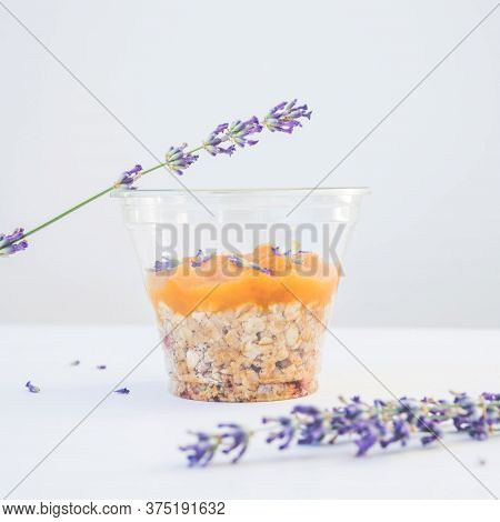 Cup Of Granola Breakfast Served With Lavender Flowers, Fruit Jam And Cedar Nuts On  A Wooden Tray. C
