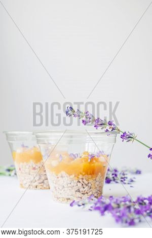 Two Cups Of Granola Breakfast Served With Lavender Flowers, Fruit Jam And Cedar Nuts On  A Wooden Tr