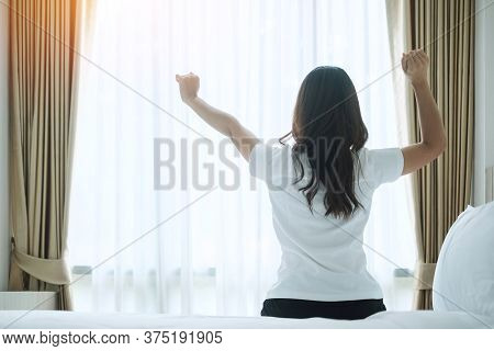Happy Woman Stretching In Bed After Waking Up, Young Adult Female Rising Arms And Looking To Window