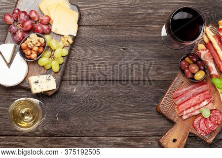 Cheese, meat, grapes and olives antipasto. Appetizer selection on wooden board and glasses with red and white wine. Top view with copy space. Flat lay