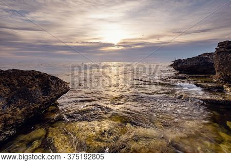 Dramatic Sunset. The Wave Flows Over Weathered Rocks And Boulders A Natural Pond In The Foreground.